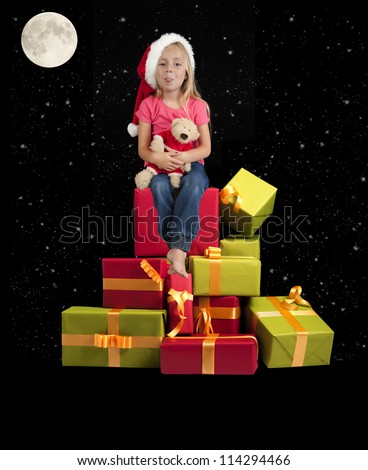 little girl with teddy bear and christmas hat on a black background - stock photo