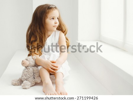 Little girl with teddy bear toy at home in white room sitting near window - stock photo