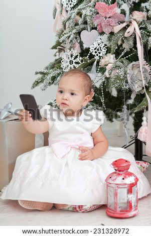 Little girl with the mobile phone sits near a Christmas fir-tree - stock photo