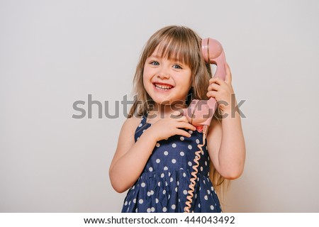 little girl with the old landline phone. little girl in polka-dot dress. girl talking on retro phone. pink retro phone. girl and pink phone. baby's calling on the phone. beautiful girl with long hair