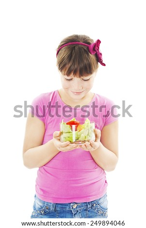 Little girl with the vegetables, looking into the bowl - healthy food concept. Isolated on white background  - stock photo