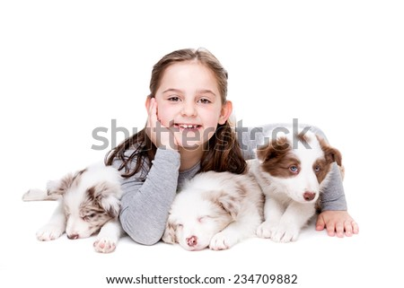 little girl with three border collie puppies in front of a white background - stock photo