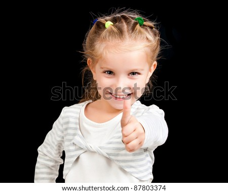 little girl with thumbs up on black background - stock photo