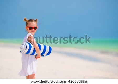 Little girl with towels on white beach vacation - stock photo
