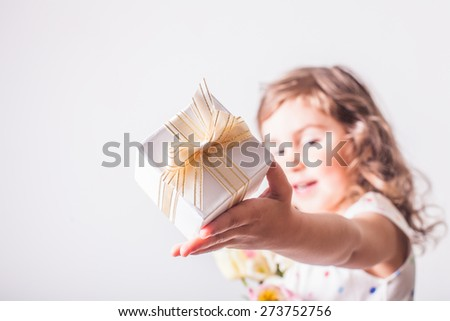 Little girl with tulips and box with present for mom - stock photo