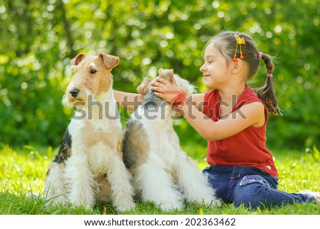 Little girl with two dogs of breed fox terrier on green lawn