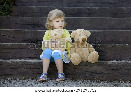 little girl with two teddy bears seated on wooden steps