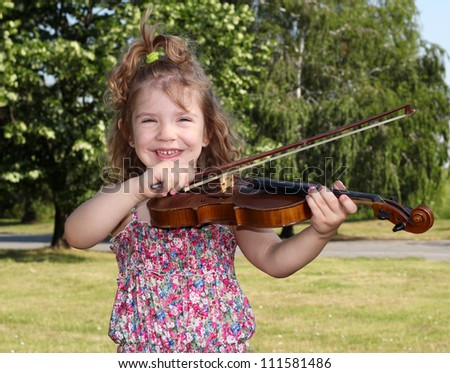 little girl with violin in park - stock photo