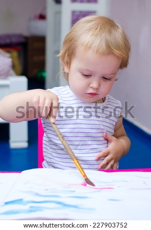 little girl with watercolor painting sitting at the table