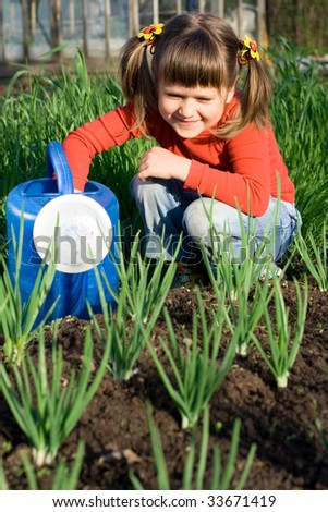 Little girl with watering can is sitting on the vegetable garden near onion patch - stock photo