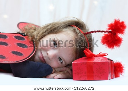 Little girl with wings and a gift - stock photo
