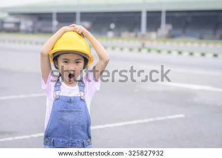 Little girl with yellow safety helmet in warehouse center background; Transportation work; Surprise pose