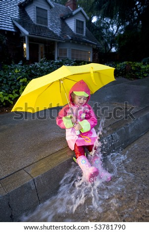 Little girl with yellow umbrella playing in rain wearing pink rain slicker and pink galoshes