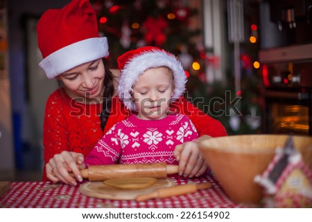 Little girl with young mother baking Christmas gingerbread cookies together - stock photo