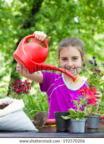 Little girl working in the garden. Planting a spring flowers - stock photo