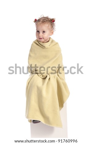 little girl wrapped in a blanket on white background