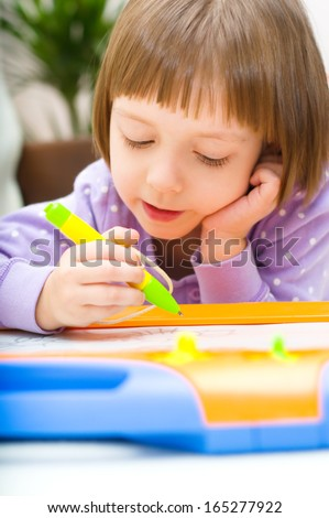 Little girl writing at magnetic drawing board - stock photo