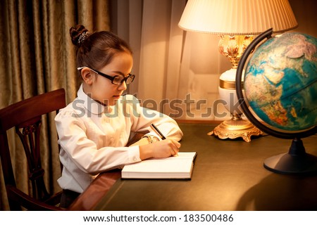 Little girl writing in notebook at desk with lamp and globe - stock photo