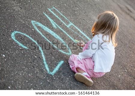 Little girl writing 2014 sitting on asphalt - stock photo