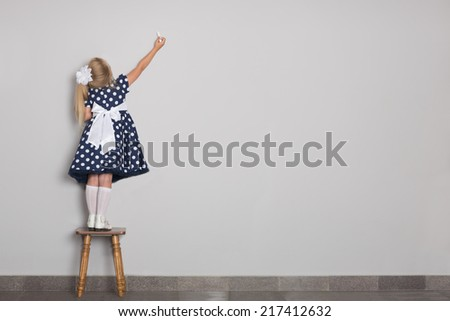 Little girl wrote in chalk on a gray wall. Girl is six years old. - stock photo