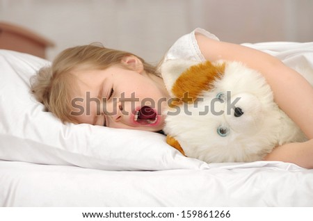 Little girl yawning while lying in bed - stock photo