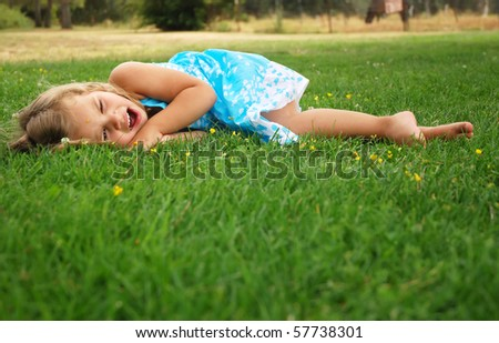 Little girl yawns while laying on the grass - stock photo