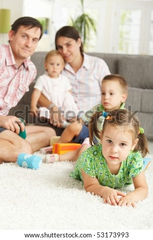Little girl (3-4 years) lying on floor at home with nuclear family in background. - stock photo