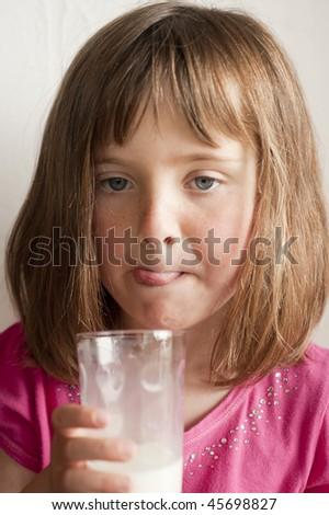 little girl (5 years old) enjoying  drinking glass of milk - stock photo