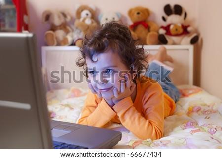 little girl, 5- 6 years old, enjoying her favorite cartoon on a laptop - stock photo
