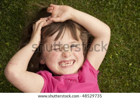 little girl (5 years old) laying in the grass - stock photo