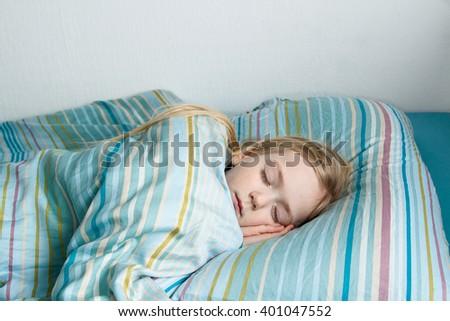 Little girl 5 years old sleeping the sweet sleep, Teal bed linen - stock photo