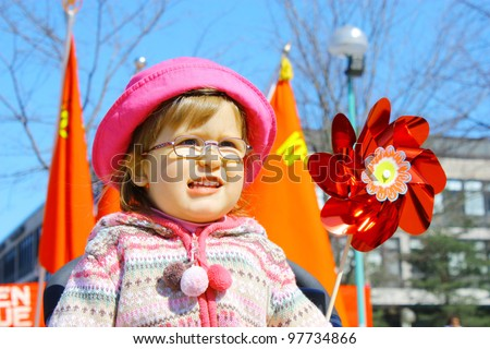 Little girl 2 years old wearing glasses in pink hat and red flags - stock photo