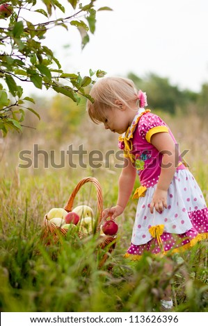Little girl 2.5 years to pick apples - stock photo