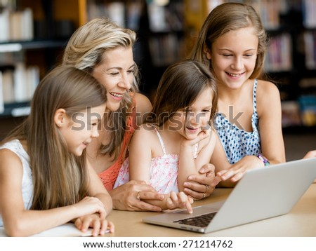 Little girls and their mum with a laptop in library - stock photo