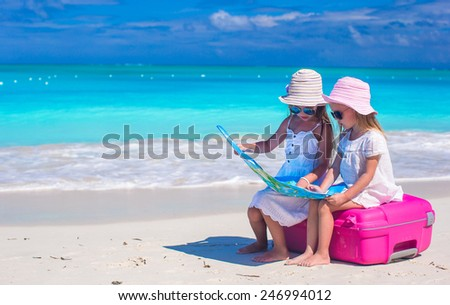 Little girls at tropical beach while summer vacation - stock photo