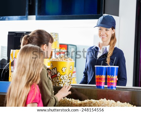 Little girls buying popcorn and drinks from female seller at cinema concession stand - stock photo