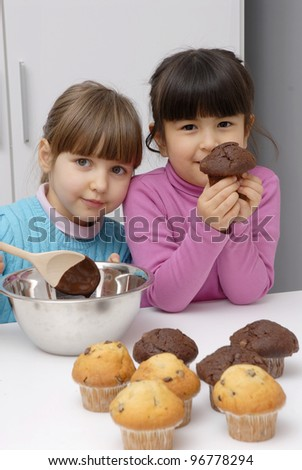 Little girls cooking chocolate and vanilla cakes. - stock photo