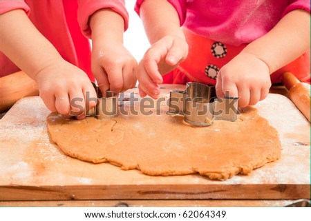 little girls cutting christmas  gingerbread cookies, hands only - stock photo