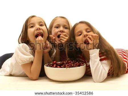 Little girls eating sweet cherries - stock photo