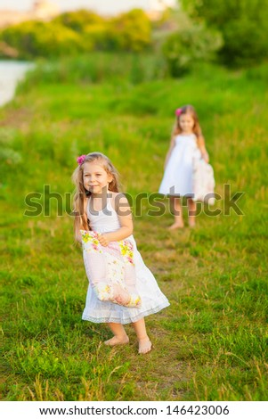 Little girls having fun with pillows and feathers - stock photo