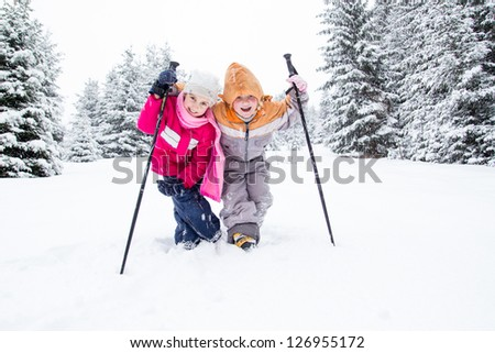 Little girls hikers spending nice time in snowy forest - stock photo