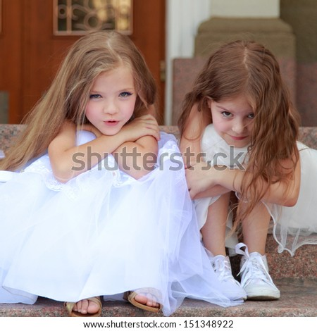 Little girls in white dresses with long hair outdoor