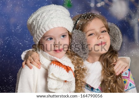 Little girls in white knitted clothes celebrating christmas
