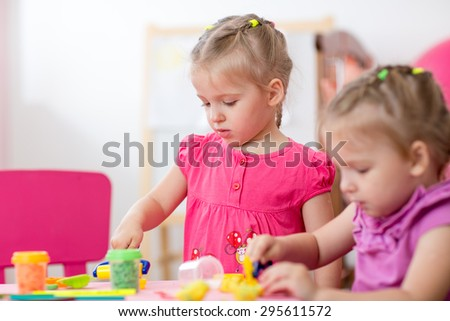 Little girls learning to work colorful play dough in nursery at home or day care center - stock photo