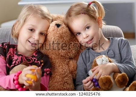 Little girls on sofa huddling up against teddy bear, smiling. - stock photo