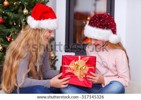 little girls opening gift christmas tree  in background - stock photo