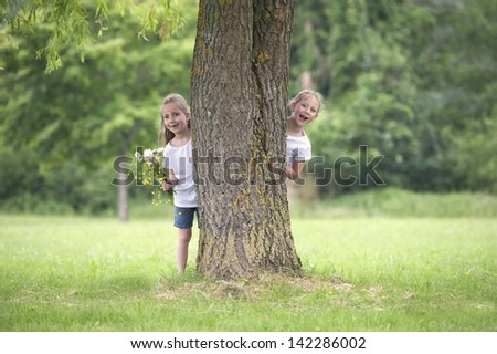 little girls playing hide and seek in the park - stock photo