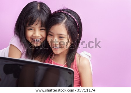 Little girls playing laptop in the bedroom with pink copy space