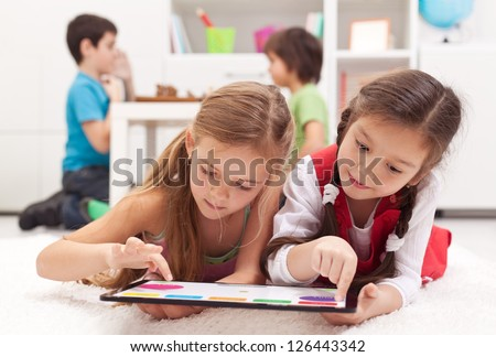 Little girls playing on a tablet computing device - laying on the floor - stock photo