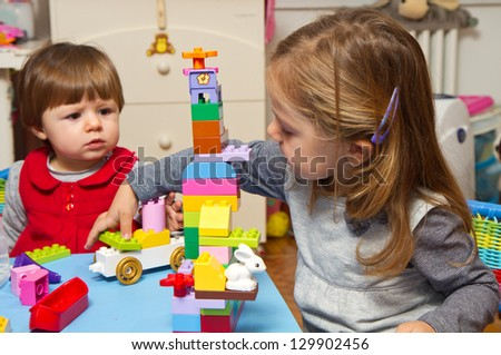 Little girls playing with building bricks - stock photo